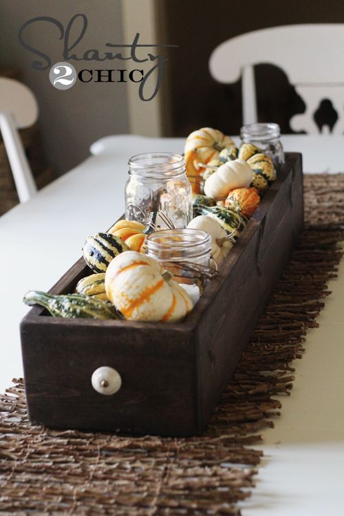 You had me at Mason Jars!!! Fill a box with votive candles in Mason jars and a variety of small gourds and you've got a haves-ready centerpiece. Blogger Whitney of Shanty 2 Chic made her own container and this project still took just an hour to make.  Get the tutorial at Shanty 2 Chic.    - CountryLiving.com
