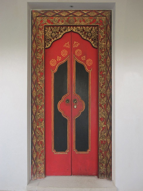 Change a rectangle door (& frame) from boring to interesting with paint and imagination. You could add depth with 1/4-inch plywood cut out and glued to the top of the door, like in this example from Bali, Indonesia