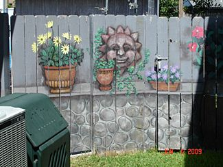 Small Side Fence with Painted Art looks like a real shelf with potted plants sitting on it!