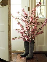 spring decor on porch... But my guys might be upset if I use their boots for concrete work and stick flowers in them. :-)