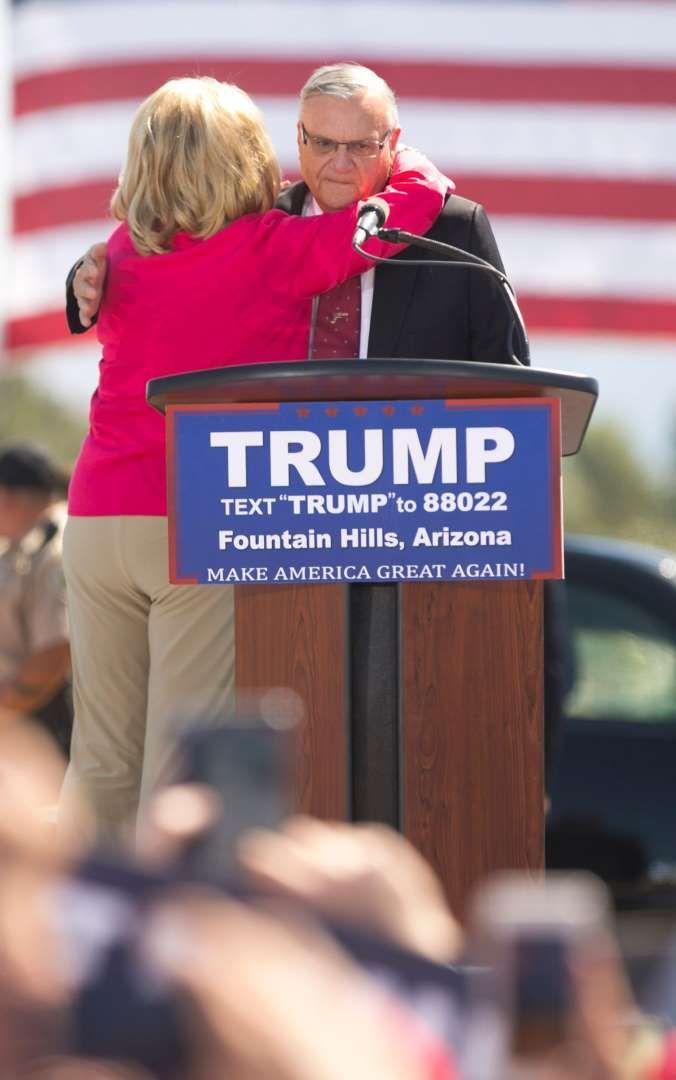 Though No Longer Sheriff, Joe Arpaio Is Still a Polarizing Figure   -  August 23, 2017:  Joe Arpaio, Arizona's controversial ex-sheriff   -  Former Arizona Governor Jan Brewer hugs Maricopa County Sheriff Jo Arpaio before Republican Presidential candidate Donald Trump speaks at his rally in Fountain Hills, Ariz. on March 19, 2016. (Via OlyDrop)