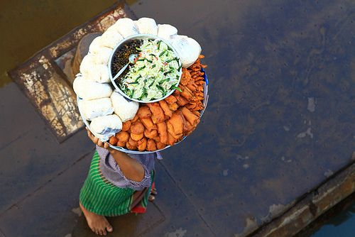"""Food vendor at the port in Galachipa, Bangladesh.  Food is prepared at home and carried to the port for sale. Here you can see a typical Bangladesh selection of local """"fastfood"""" ... the white bags contain puff rice, various fried vegetables, cucumber-cabbage-chili salad and a sort of chickpeas."""