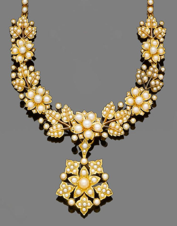 A late 19th century seed pearl necklace, circa 1890. The tapering front of floral and foliate design set throughout with bouton and seed pearls, terminating in a similarly-set detachable flowerhead pendant, to a seed pearl back-chain, lengths: necklace 39.5cm, pendant 3.1cm