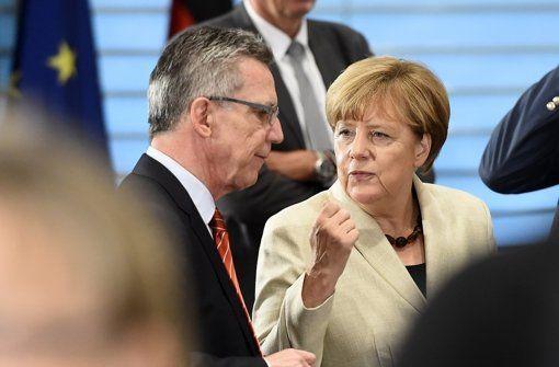 Innenminister Thomas de Maizière bespricht sich mit Angela Merkel im Bundestag. In seiner Rede versuchte er, die Flüchtlingskrise menschlich zu sehen. Foto: AFP