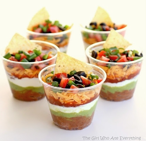 Individual seven layer dips. Smart idea for a cocktail party with passed appetizers.