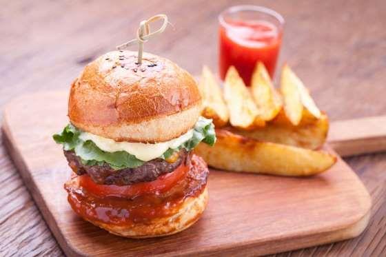 Trop facile à faire ce burger, même pour les campeurs.  - 2 c à s de moutarde - 3 c à s de ketchup - Fromage (en option) - Quelques cornichons spécial sandwich - 2 tomates - 4 steaks hachés - 2 oignons - De la salade iceberg ou laitue - 4 pains hamburger   Étape 1 :  Cuire les steacks hachés. Hacher les oignons, les tomates en rondelles et les cornichons en petits cubes. Étape 2 :  Préparer la sauce en mélangeant le ketchup et la moutarde.  Étape 3 :  Dans une poêle, chauffer 1 c à s d'huile…
