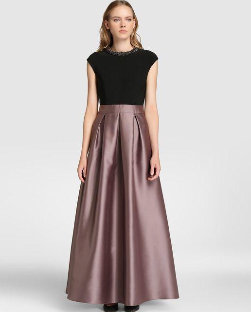 Vestido largo, con efecto top y falda. Cuerpo en color negro, de manga corta caída y escote redondo con adorno tipo collar. Falda larga satinada con lazo en la cintura.