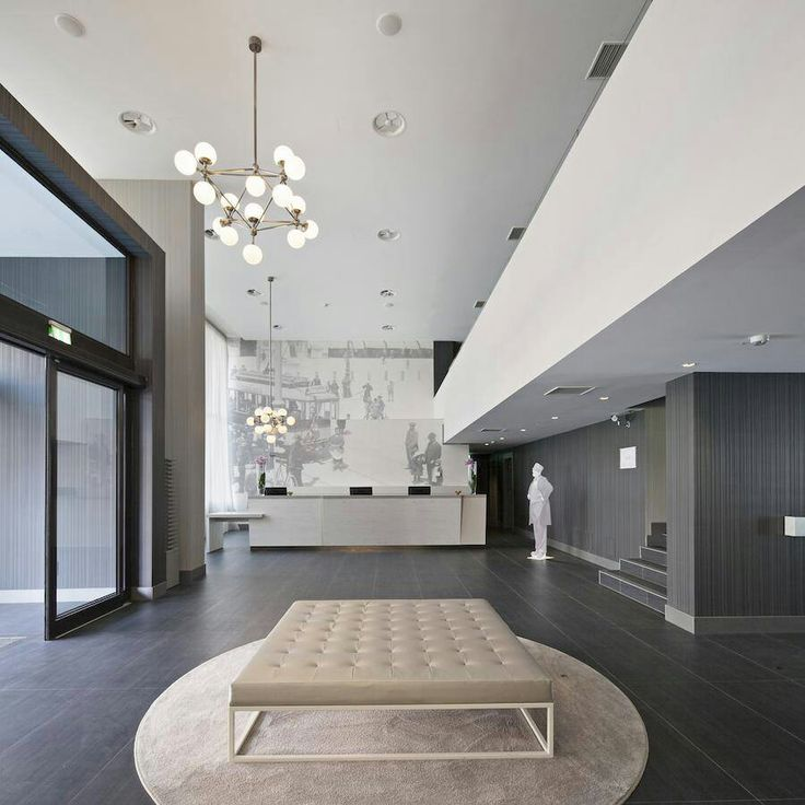 #ISAACLIGHT curates the lighting project for NH HOTEL GROUP. Shot of the reception. An assembly of minimal design, soft lights and colours. Design and products made in Italy. Parma Italy