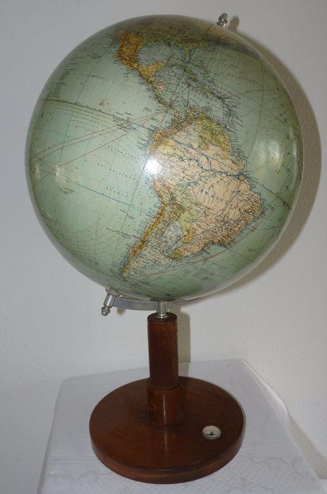 Grote antieke aardglobe van Columbus model 200  Ca. 1925 DuitslandFraaie gedetailleerde globe met veel geo-politieke informatie over de periode net na de 1e wereldoorlog. Deze globe is afkomstig uit Duitsland waar hij werd gemaakt door de bekende globemaker Columbus uit Berlijn. De globe is gemaakt van karton met papieren stroken waarop de grafiek is gedrukt en hij heeft een diameter van 33 cm. Hij is geplaatst op een houten voet met een werkend kompas. De hoogte is ca. 55 cm.De globe is…