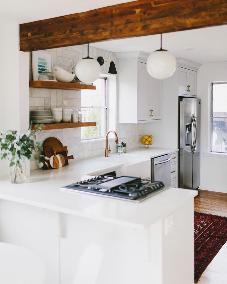 Bright white kitchen with open shelves, natural ceiling beam and printed rug.