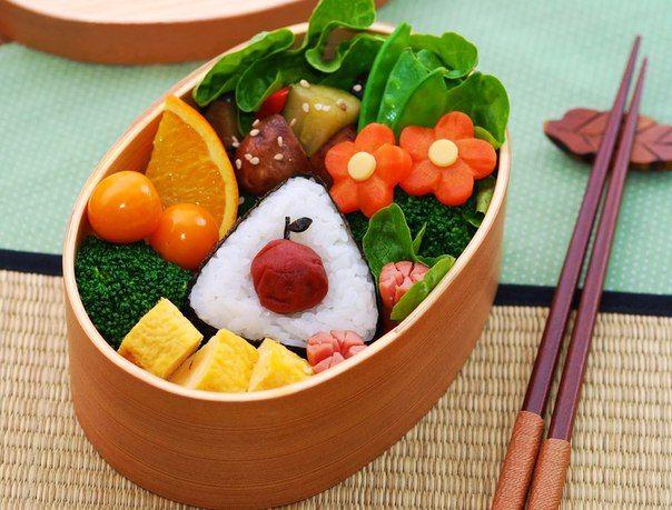 Бэнто с умэбоси в виде яблока и апельсином<br><br>Полное содержание: <br>- онигири с умебоши <br>- жареные овощи (перец, цуккини и баклажаны)<br>- жареные грибы<br>- бланшированная капуста брокколи<br>- кусочек апельсина<br>- два физалиса<br>- два цветка из моркови<br>- сахарный горох<br>- листья..