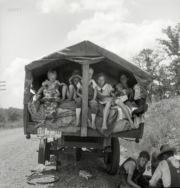 "Arkansas Travelers: June 1938. ""On highway No. 1 of the 'OK' state near Webbers Falls, Muskogee County, Oklahoma. Seven children and eldest son's family. Father was a blacksmith in Paris, Arkansas. Son was a tenant farmer. 'We're bound for Kingfisher (Oklahoma wheat) and Lubbock (Texas cotton). We're not trying to but we'll be in California yet. We're not going back to Arkansas; believe I can better myself'."" Photo by Dorothea Lange"