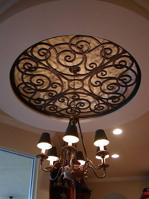 Faux Wrought Iron Ceiling Medallion Over Chandelier. love it but I would make the chandelier as fine as the iron ceiling.