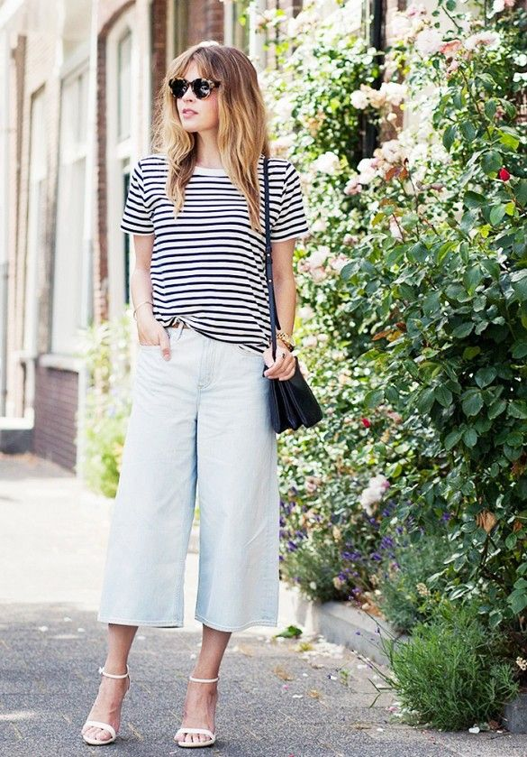 A striped t-shirt is worn with denim culottes, white strap sandals, sunglasses, black crossbody bag and a gold watch.