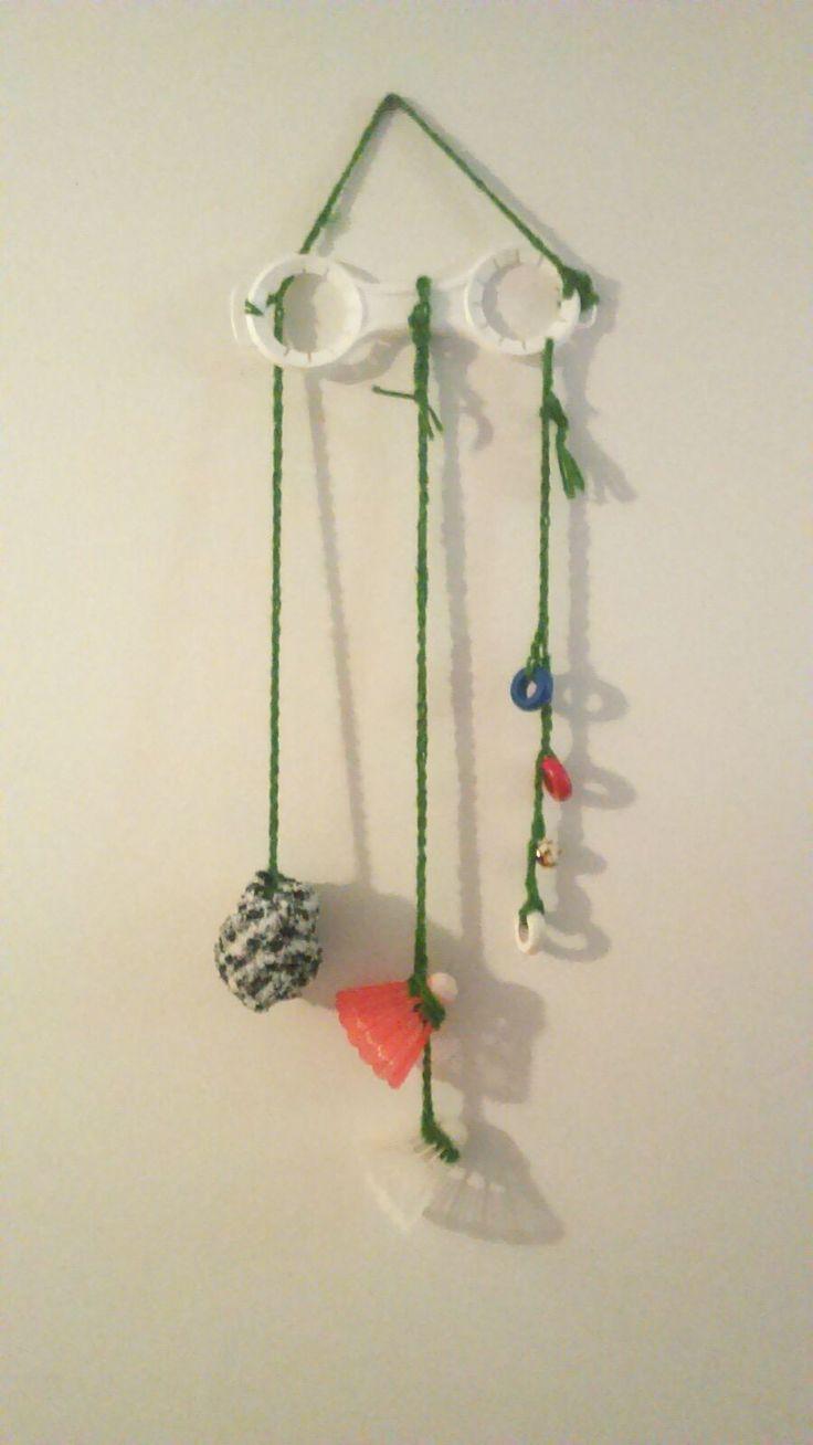 Mobile bébé fait main avec des petits anneaux de couleurs, une chaussette douce, balle de badminton et des grelots. Thérèse Éliane