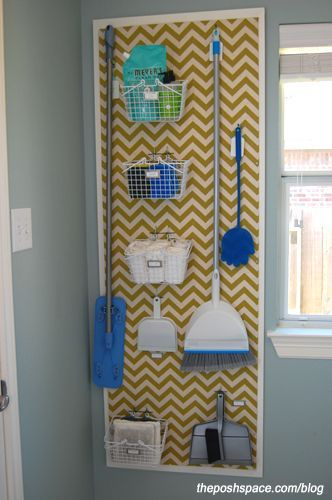 DIY corkboard organize brooms and mops and cleaning supplies in the laundry room with a peg board.