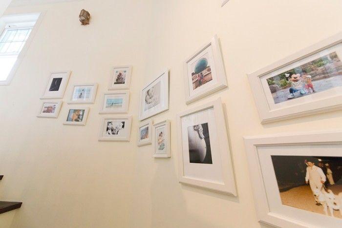 2階へ上がる階段の壁には、家族の思い出の写真が飾られている。ここは白のフレームで統一してスッキリと見せている。