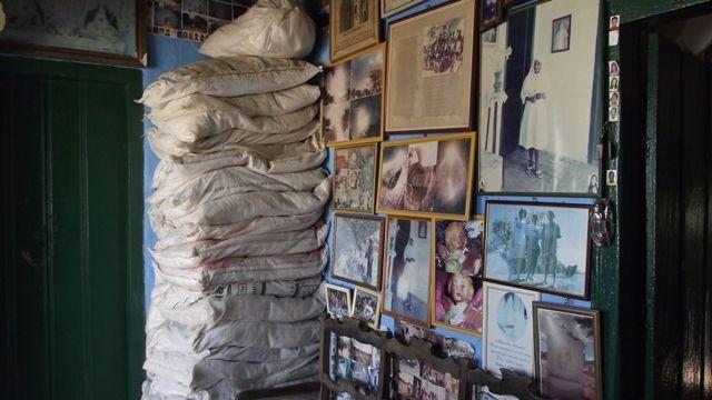 Sacos ao fundo com bilhetes e cartas ex-votivas, parede lateral com imagens fotograficas emolduradas.