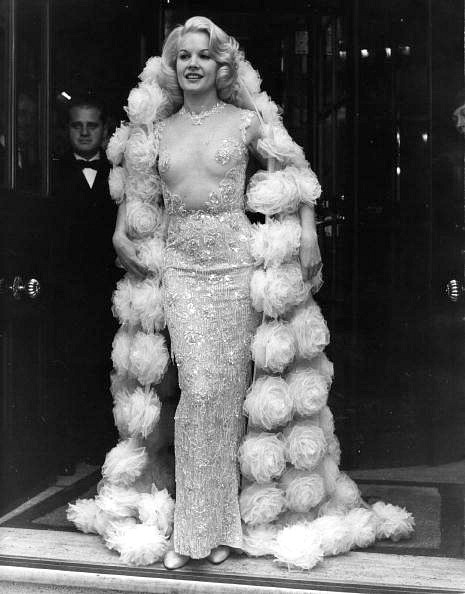 """Actress Carroll Baker in transparent beaded gown with tulle rosette wrap designed by Pierre Balmain to wear to the premiere of her film """"The Carpetbaggers"""". June 1964"""