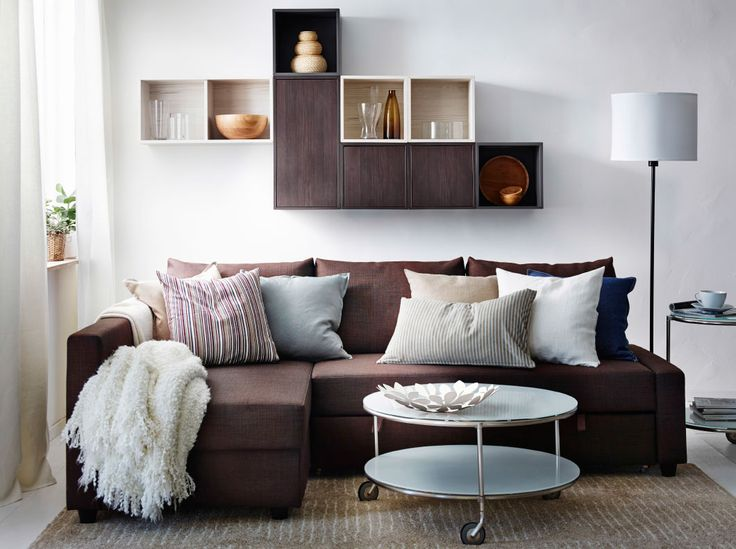 A modern living room with a brown FRIHETEN sofa bed, VALJE wall cabinets in brown and white and a white STRIND coffee table.