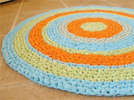 Colorful and festive rag rug.   *Round rag rug, scatter rug, mat, bathmat, more.   *Colorful fun and cheery for a variety of settings.   Would be perfect in childrens room and play areas.   *Hand crocheted from *clean*, used recycled fabric and bed linens made from cotton and cotton blend fabrics.   Colors: (shown here in natural and incandescent lighting, and may vary from monitor to monitor  please refer to color descriptions):   -Bands of all solid colors:   Bright, clear orange…