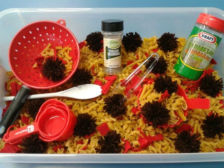 """pasta dinner"" sensory bin: uncooked pasta (any kind except spaghetti because it easily breaks), brown pom poms, colanders, empty parmesan cheese containers, spoons, etc."