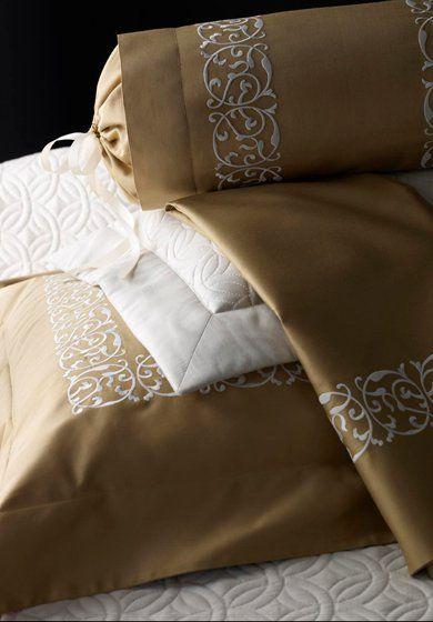 Arabesque:  The even rhythm of this exuberant arabesque scroll murmurs the Art Nouveau period when the design of linens found perhaps its richest expression. Shown here with coordinating quilted coverlet and shams.