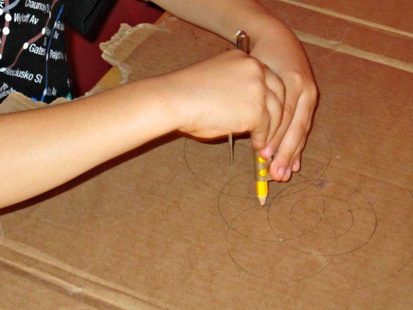 Drawing with a compass: At first he had a really hard time keeping the compass point steady. We figured out that a piece of cardboard worked much better than plain paper...