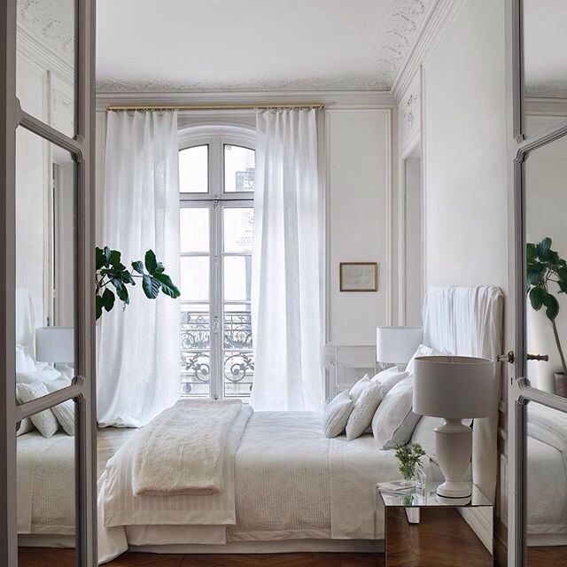 White drapes are beautiful on this arched window. Love the tall ceiling height.