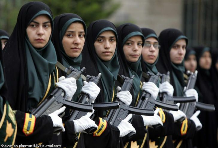 Iranian soldiers.  Just when you thought you have seen it all. Here we have a line of Iranian female soldiers. They are dressed in green and black Hijabs. The white gloves are a sharp contract to the deadly weapons.