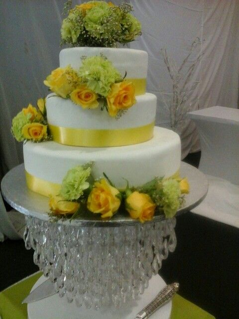 Yellow and white wedding cake with fresh flowers