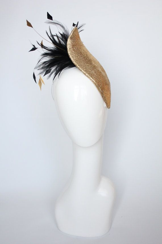 This unique cocktail hat is both elegant and striking with the sumptuous gold base off setting the spray of black and gold feathers, which