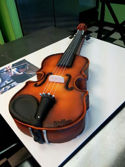 A violin cake with an edible image of the birthday boy playing the violin.