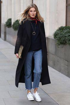 Street style look com sobretudo preto, calça jeans cropped, converse branco e bandana vermelha.