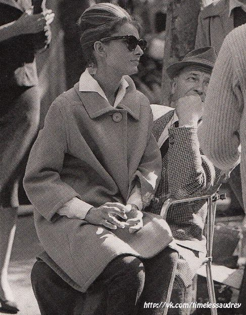 "The actress Audrey Hepburn photographed (sitting on the lap of an unidentified man, in front of the building that was rented to be Holly Golightly's apartment, on 167 East 71st Street, in Manhattan) in New York City, New York (USA), during a break in the filming of ""Breakfast at Tiffany's"", in November 1960."