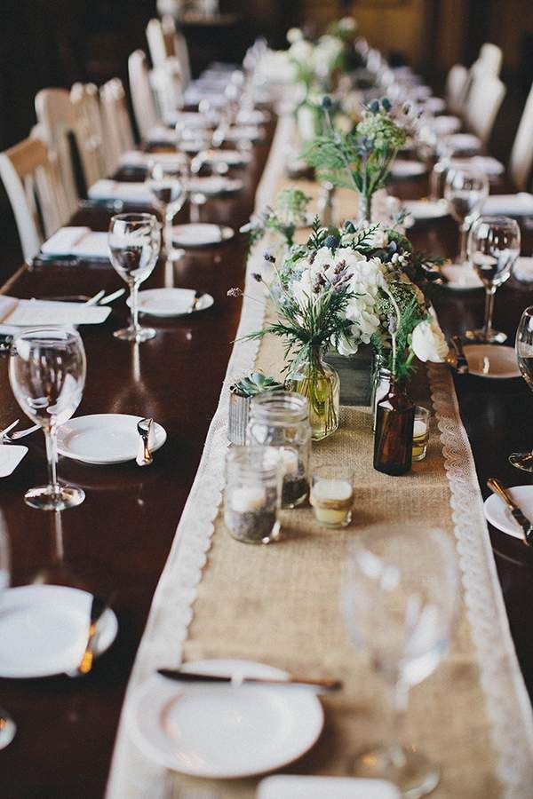 Herbs, flowers, and candles in glass jars on a long reception table.