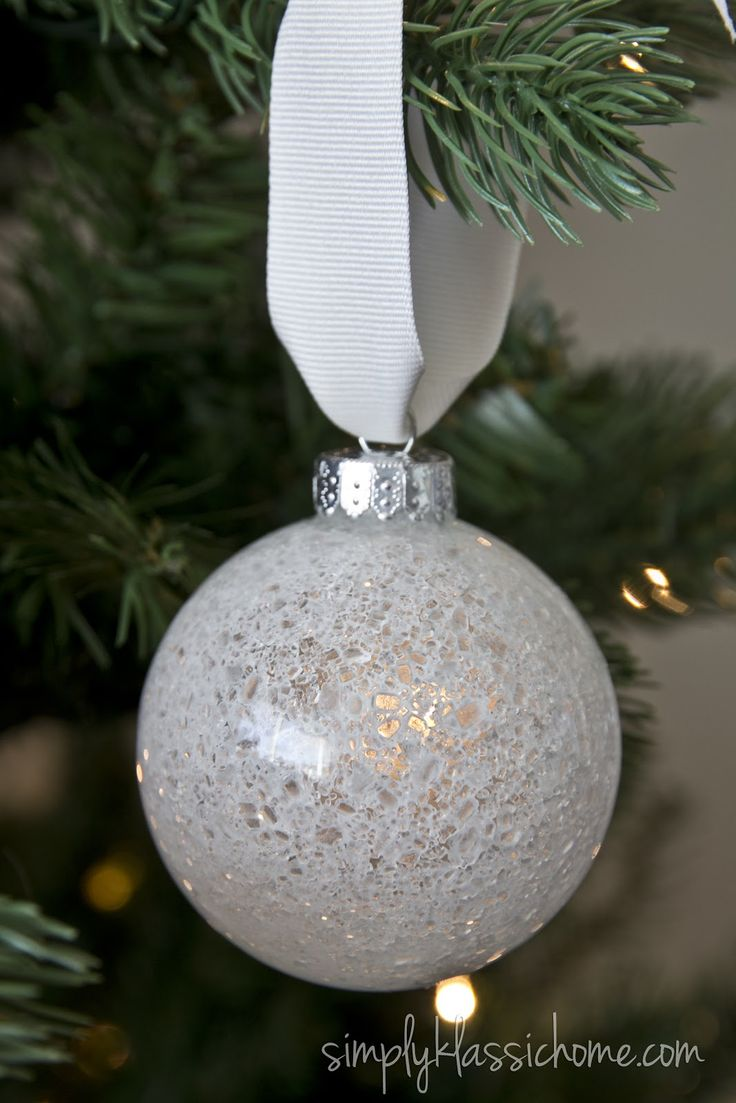 "DIY ""crackled cystal"" snowball ornament: Add a little water to a bowl of Mod Podge, just enough to thin it out a bit. Pour a little in a clear glass ornament, swirl it around to coat the inside, and let the excess drip out. Pour some epsom salt into the ornatment (and maybe a bit of silver gitter as well?), shake it up to coat the inside of the ornament. Let dry and voila!"