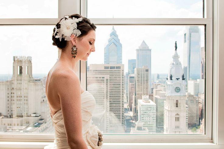 Bride by window with skyline view at Loews Hotel, Philadelphia
