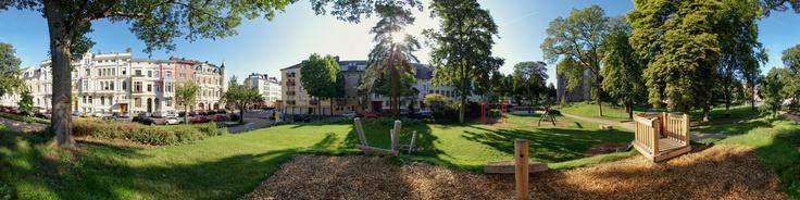 Das Panorama zeigt die Burg Frankenberg (Frankenburg) an der Straßenecke Bismarckstraße, Goffartstraße und Haßlerstraße in dem berühmten Frankenberger Viertel in Aachen, Deutschland. An der Straßenecke steht eine Litfaßsäule. Die Frankenburg ist umgeben von einem Park mit Kinderspielplatz, Baseball- und Fußballplatz und Treffpunkt von Jung und Alt. In der Bismarckstraße befindet sich ein Eiscafé, Restaurants, Kneipen, ein Biergarten, Supermärk...