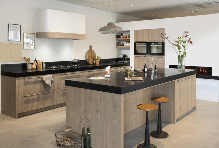 Houten keuken met mat wit stucwerk voor een mooi contrast. Het dikke zwarte blad met de brede kookzone is de finishing touch. De branders van PITT cooking zijn in het werkblad geïntegreerd: mooi en praktisch. Keuken Ardore via Grando