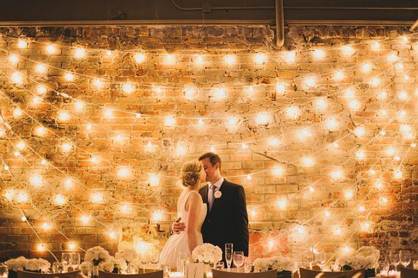 Lighting Backdrop for head table. Are those big round vintage bulbs against that brick wall?