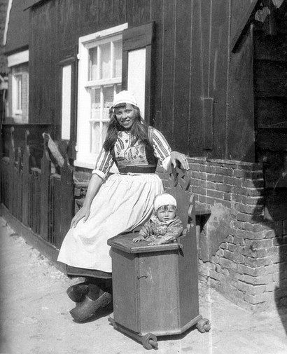 Marken. Dutch girl, wooden shoes and a baby in a cabinet on wheels.  Ca 1900