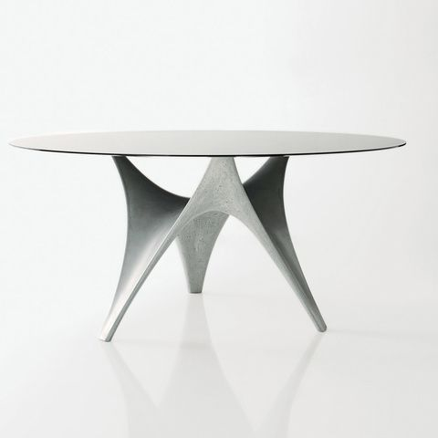 The sculptural Arc Table designed by Foster and Partners for Molteni & C consists of a solid base of cement and fiber that mimics the sweeping curves and crests of a tensile fabric structure. Weatherproof, too! dwell.com