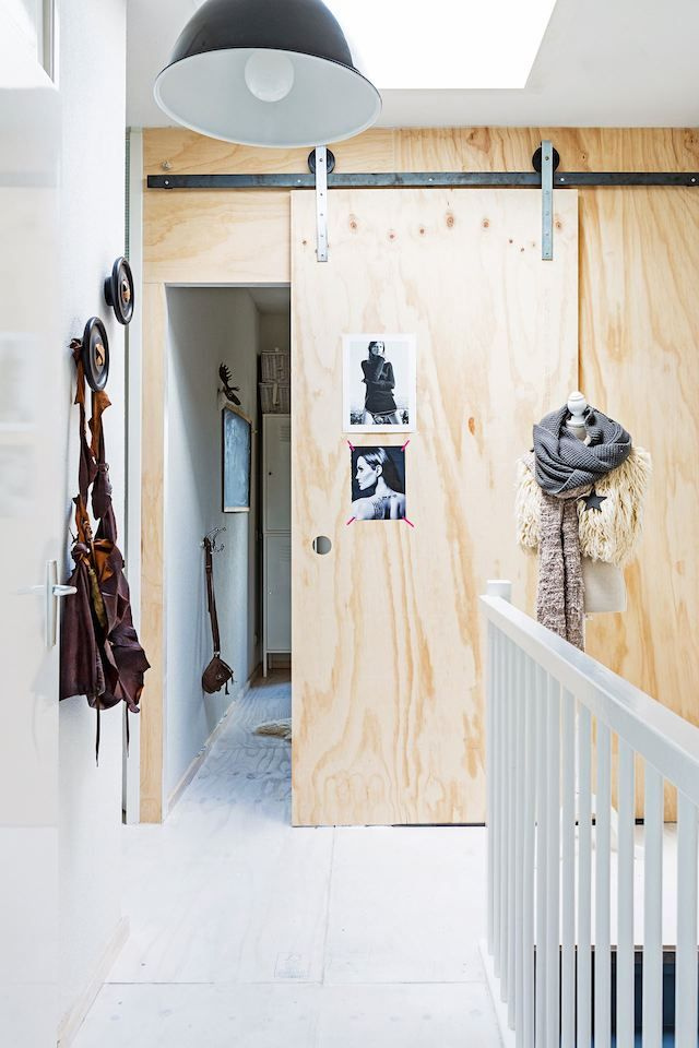 Sliding wood door on tracks in the fuss-free and laid back Dutch home of Marieke Rusticus.