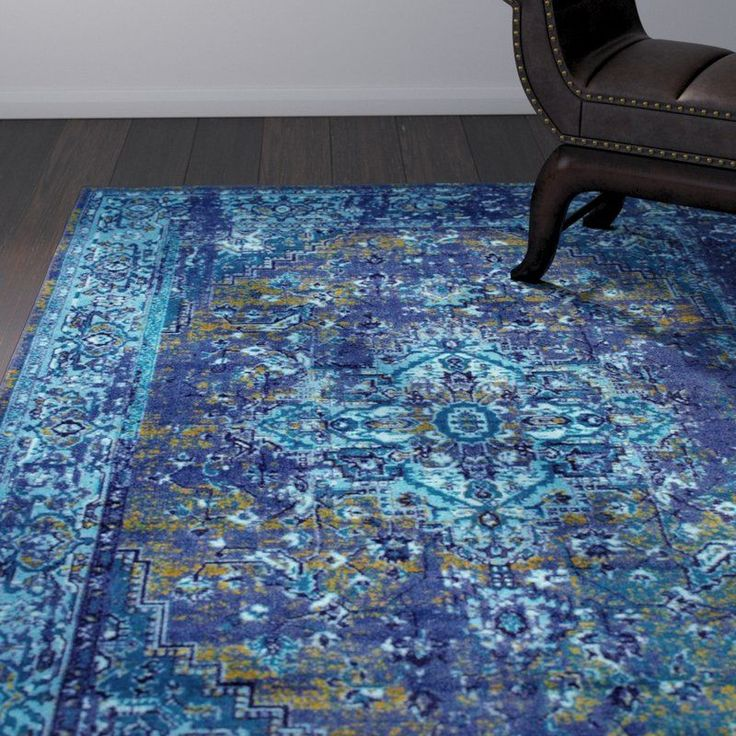 Set an Eastern-influenced foundation for an eclectic aesthetic with this charming ornate area rug. Machine woven in Egypt from easy-to-clean nylon with a slip-resistant latex backing, this charismatic design showcases an overdyed Persian-inspired motif in vibrant hues of blue. Establish an eclectic aesthetic by rolling this rug out in to define the space, then arrange a button-tufted velvet tuxedo sofa and a leopard skin slipper chair around an ornately carved mahogany coffee table. Set…