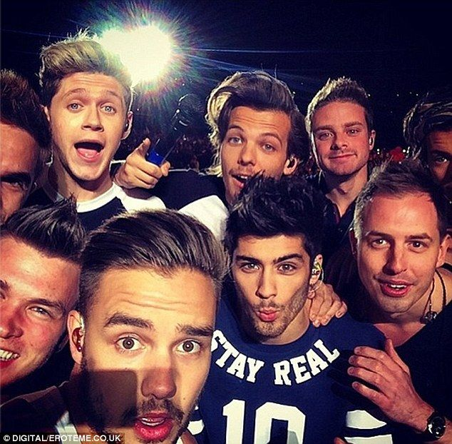 Squeeze in! Liam Payne takes a One Direction selfie on stage with their band