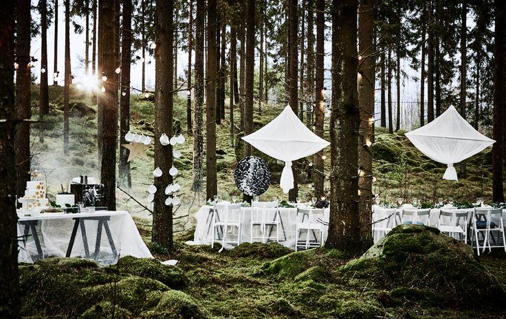 """Unsere """"Waldhochzeitstafel"""" mit einem langen, weißen Tisch, weißen Stühlen, Hängedekorationen und einem Tisch für die Hochzeitstorte"""