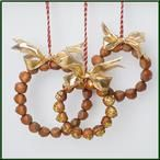 Leuke Kerst decoratie van hazelnoten Maak de hazelnoten goed droog en lijm ze rond een dekseltje om een mooie ronde vorm te behouden. Wees niet te spaarzaam met de lijm en druk de noten goed tegen elkaar. Bevestig het ophang draadje eraan en maak dan een strikje van het lint. Je kunt evt. nog wat glitterts aan de onderkant (puntige kant) van de nootjes aan.
