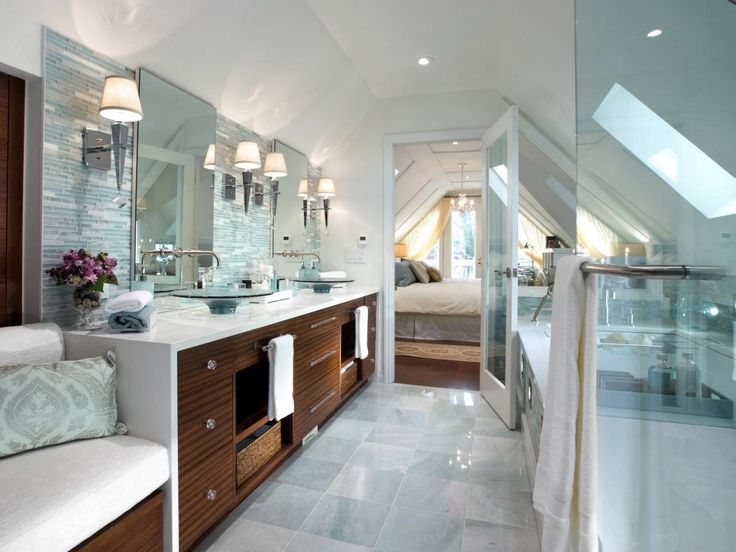 Candice began this attic transformation by gutting the space, and then dividing it into three zones: a bedroom, dressing area and master bathroom. To create a spa-like feel, she added a soaker tub; a frameless shower enclosure; a new toilet (complete with heated seat and LED lights); and luxurious finishes, including marble, glass mosaic tiles and a crystal chandelier. A new skylight also helps illuminate the many amenities in this divine bathroom.