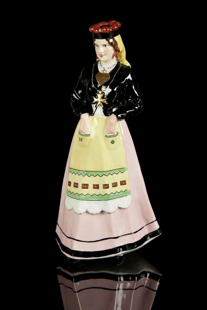 Mulher de Avintes, garrafa em porcelana da Vista Alegre. Modelo e decoração criados em 1933. Decoração policromada, pintada à mão. Marca nº 31 (1924-1947). Alt. aprox.: 29 cm.